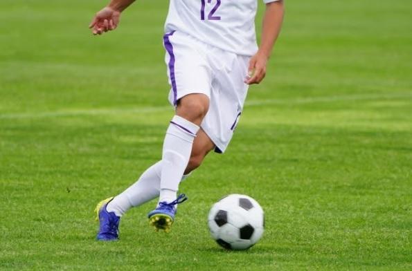 パスをトラップするサッカー選手