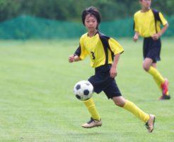 パスをトラップするサッカー少年
